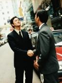Executive pair shaking hands on street. - Jack Hollingsworth
