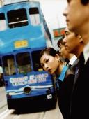 Executives waiting for bus, female executive looking at camera. - Jack Hollingsworth
