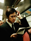 Executive in train reading newspaper. - Jack Hollingsworth