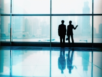 Executive pair in front of large window, silhouette. - Jack Hollingsworth