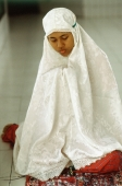 Indonesia, student clutches her Koran beneath a prayer shawl. - Steve Raymer