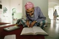 Malaysia, Penang, Muslim scholar studies Islamic histories at Kapitan Kling Mosque. - Steve Raymer