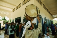 Cambodia, Kompong Cham, Muezzin of a mosque beats a kouv (drum) to summon worshippers to Friday prayers. - Steve Raymer
