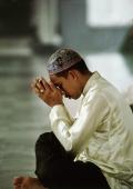 Malaysia, Kuala Lumpur, Malay man holds a small Koran and prays. - Steve Raymer