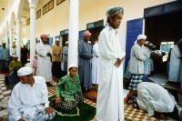 Cambodia, Kompong Cham, bowing Muslim worshippers spill outside main prayer hall. - Steve Raymer