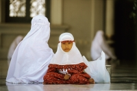 Indonesia, Aceh,Banda Aceh,Muslim girl dressed in mukenahs or kerudungs (prayer robes) sits with mother at Baiturrahman Great Mosque. - Steve Raymer
