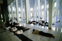 Malaysia, Kuala Lumpur, men resting after Friday Prayers in the National Mosque. - Steve Raymer