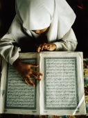 Malaysia, Selangor, Malay girl reading the Koran written in Jawi, the Malay language written in Arabic script. - Steve Raymer