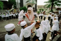 Indonesia, Riau Islands, Tanjung Pinang, Muslim teacher playing with students. - Steve Raymer