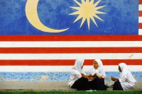Malaysia, Kukup, three Muslim schoolgirls chatting in front of a large Malaysian flag painted on the wall behind them. - Steve Raymer