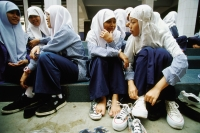 Indonesia, Jakarta, Muslim students gossiping and putting on shoes after noontime prayers. - Steve Raymer