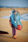 Malaysia, Marang River, fisherman walks along the beach carrying net and bucket. - Steve Raymer