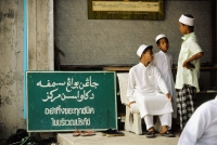 Thailand, Yala, Muslim children sit next to a sign cautioning worshippers to dispose of their trash before entering the mosque. - Steve Raymer