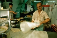 Singapore, a Muslim chef tossing murtabak, a thick pancake stuffed with meat, egg and onions at a food stall on Arab Street. - Steve Raymer
