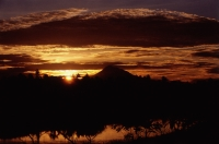 Indonesia, Sumatra, Aceh, The sun setting over the mountains. - Steve Raymer