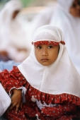 Indonesia, Aceh, Banda Aceh, Muslim girl dressed in mukenahs or kerudungs (prayer robes) sits at Baiturrahman Great Mosque. - Steve Raymer