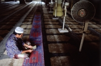 Singapore, A Muslim man reading in the quiet of a Mosque along Arab Street. - Steve Raymer