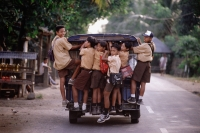 Indonesia, Lombok, Schoolboys riding on the back of a van. - Steve Raymer