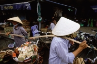 Vietnam, Ho Chi Minh City, District One, Women carrying goods to be sold. - Steve Raymer