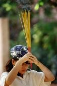 Vietnam, Ho Chi Minh City, A woman waving incense sticks during prayer. - Steve Raymer