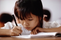 Vietnam, Ho Chi Minh City, A young girl concentrating on her studies. - Steve Raymer