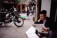 Vietnam, Hanoi, An elderly man sitting in a doorway reading a Vietnamese newspaper. - Steve Raymer