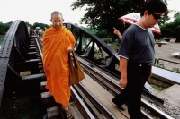 Thailand, Kanchanaburi, River Kwai, A monk walking over the bridge, along with other tourists. - Steve Raymer