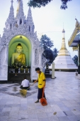Myanmar (Burma), Yangon (Rangoon), Man sweeping tiles at Shwedagon Pagoda, man praying in background. - Steve Raymer
