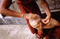 Myanmar (Burma), Yangon (Rangoon), One monk helping another shave his head. - Steve Raymer