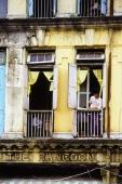 Myanmar (Burma), Yangon (Rangoon), A man looking out of a window in an old colonial building. - Steve Raymer