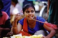 Myanmar (Burma), Yangon (Rangoon), A vendor in a market fanning the humid air to keep flies away from her sliced pineapple. - Steve Raymer