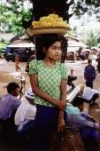 Myanmar (Burma), Yangon (Rangoon), A vendor balancing a platter of fruit on her head in a market in Yangon. - Steve Raymer
