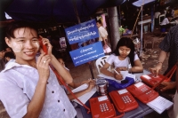 Myanmar (Burma), Yangon (Rangoon), A woman wearing homemade makeup makes a telephone call at an open-air public phone station. - Steve Raymer