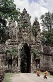 Cambodia, Siem Reap, Buddhist monks on motorcycles riding into Angkor - John McDermott
