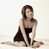 Young woman in black dress sitting, portrait - Erik Soh