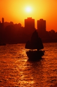 Hong Kong, Victoria Harbor, Silhouette of boat, sun in background. - Jack Hollingsworth