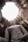 Thailand, Sukothai, Large statue of Buddha inside temple with open roof - John McDermott