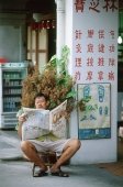 Singapore, Chinatown, Man sitting on stool reading local Chinese newspaper. - Steve Raymer