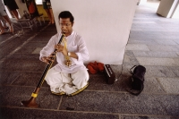 Singapore, Little India, Man sitting on floor playing clarinet. - Steve Raymer