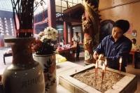 Malaysia, Kuala Lumpur, Chinatown, Man lighting joss sticks at Chinese temple. - Steve Raymer