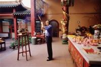 Malaysia, Kuala Lumpur, Chinatown, Man praying with joss sticks at Chinese temple. - Steve Raymer