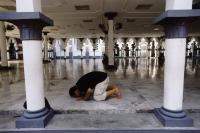 Malaysia, Kuala Lumpur, Muslim man praying at National Mosque (Masjid Negara). - Steve Raymer