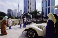Malaysia, Kuala Lumpur, Muslim girls taking a picture with vintage car in downtown Kuala Lumpur. - Steve Raymer