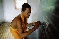 Vietnam, Mekong Delta region, Bac Lieu, Buddhist monk of Khmer origin writing on blackboard. - Steve Raymer