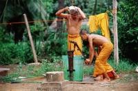 Vietnam, Mekong Delta region, Bac Lieu, Buddhist monks bathing at water pump. - Steve Raymer