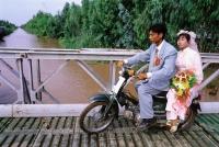 Vietnam, Mekong Delta region, Long Xuyen, Bride and groom on moped crossing bridge. - Steve Raymer