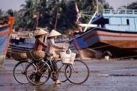 Vietnam, Women on bicycles wait for fishing boats to dock - Jill Gocher