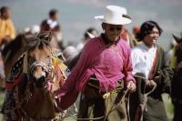 China, Szechuan (Sichuan), Kham region, Nomad man in traditional silk shirt leading horse at summer festival. - Jill Gocher