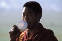 China, Szechuan (Sichuan), Kham region, Tibetan monk blowing on conch shell as a prayer call during the summer nomad festival. - Jill Gocher