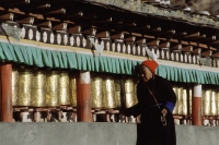 China, Szechuan (Sichuan), Kham region, Tibetan woman making kora with prayer wheels. - Jill Gocher